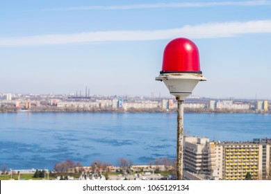 Obstruction Lights close-up. Light-signaling is based on a blue sky and a river. Red alarm lamp.