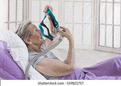 Obstructive sleep neap therapy,Woman adjusting CPAP mask .
