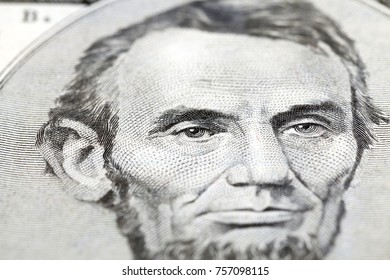 obverse of an American banknote five dollars, focus on the eyes of the president, close-up