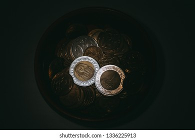 The obverse, reverse and edge of the Egyptian coin lie in the dark among the coins of other countries and are illuminated by a ray of light.