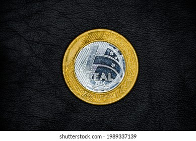 Obverse of used and old Brazilian 1(one) Real coin, minted in 2014, on black leather background. The Southern Cross.