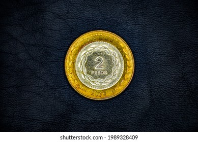 Obverse of used, old and damaged Argentine 2(two) pesos coin, minted in 2016, on black leather background.