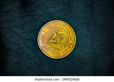 Obverse of used, old and damaged Nicaraguan 25(twenty five) centavos(cents) coin, minted in 2014, on black leather background.