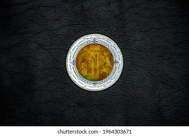 """Obverse of used and old Mexican 1(one) peso coin, minted in 2018, on black leather background. Stylized image of the """"Ring of Splendor of the Sun Stone."""""""