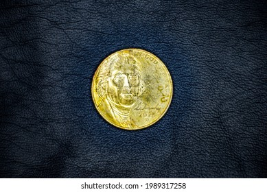Obverse of used and old United States 5(five) cent(nickel) coin, minted in 2013, on black leather background. Portrait of Thomas Jefferson.