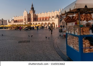 Obwarzanek krakowski street vendor in the main market square with Cloth Hall in the background, Krakow, Poland