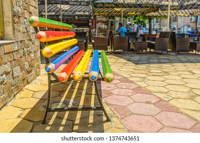 OBZOR, BULGARIA - JUL 22, 2018: Central square. A bench of colored pencils.  Architecture and streets of the town of Obzor in Bulgaria.