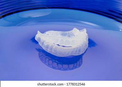Occlusal splints for protection of teeth of people prone to nocturnal bruxism on blue background
