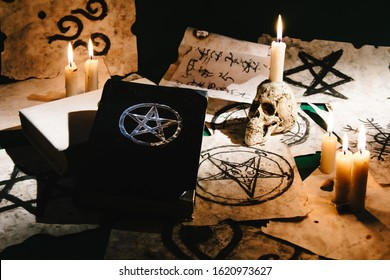 Occult grimoire, black magic book laying on table with occult symbols, candles, pentagrams, fortune telling, ritual, altar, spiritism, secret knowledge, scull