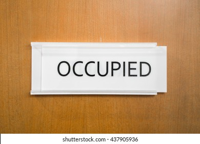 Occupied (Busy) sign in front of the meeting room wooden door in an office