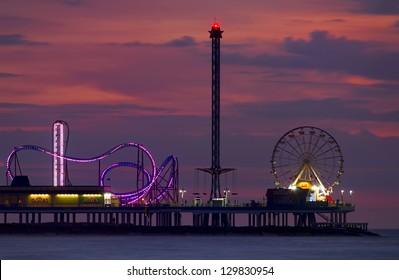 Ocean amusement park rides viewed at dusk