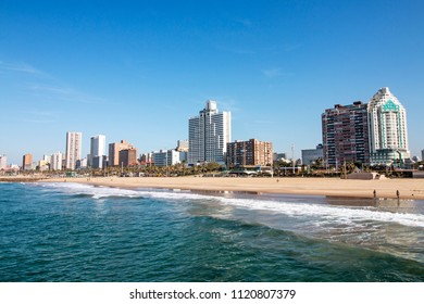 Ocean and beach against Golden Mile coastal city skyline and blue sky in Durban, South Africa