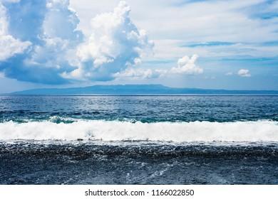 Ocean beach with black volcanic sand against cloudy blue sky. Summer landscape black beach in Bali, Indonesia