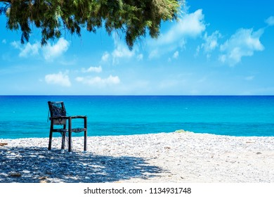 Ocean beach and chair on the Crete in sunny day