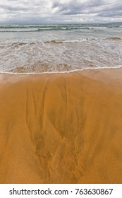 ocean beach viewed with water washing ashore over rich yellow sand