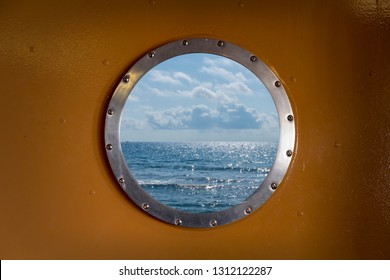 Ocean and blue cloudy sky seen through the porthole of a ship