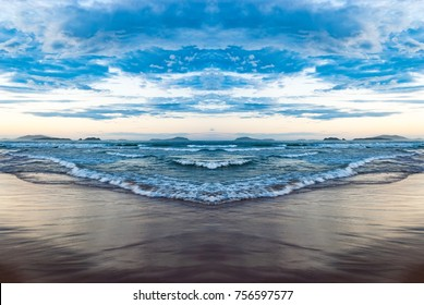 Ocean with blue water, waves, foam and wake. Summe day tropical beach. Twilight hour view at sky and clouds. Image with symmetry filter for travel vacation concept, design templates, lifestyle blog