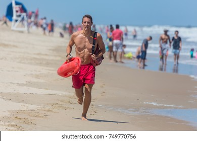 OCEAN CITY - JUNE 17: Lifeguard running on the beach in Ocean City, MD on June 17, 2016. Ocean City, MD is a popular beach resorts on East Coast and one of the cleanest in the country.