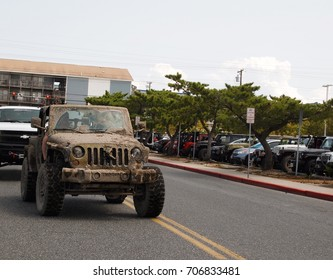 OCEAN CITY, MD - AUGUST 26, 2017: A vintage Jeep covered thick dried mud arrives at the Roland E. Powell Convention Center on Saturday afternoon of Jeep Week in Ocean City, MD.