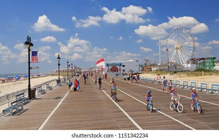 OCEAN CITY, NEW JERSEY - AUGUST 05, 2018: People walking and biking along the famous boardwalk in Ocean City, New Jersey, USA.