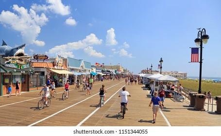 Ocean City, NJ - August 05, 2018: People walking and biking along the boardwalk in Ocean City, New Jersey, USA