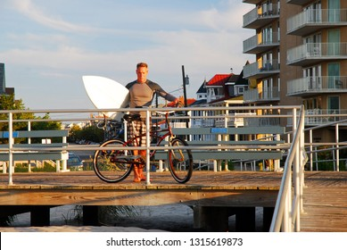 Ocean City, NJ, USA August 24, 2013 An adult man parks his bike before going surfing at Ocean Beach, New Jersey