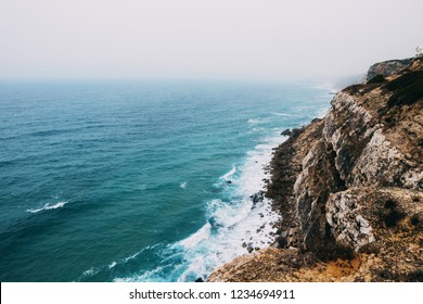 Ocean coast line cliff in a cloudy fogy day.Aerial view of waves breaking to the rocky shore of Atlantic ocean in Portugal
