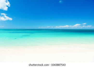 Ocean coast on antigua island in caribbean. Ocean with turquoise water, white sand and sunny blue sky