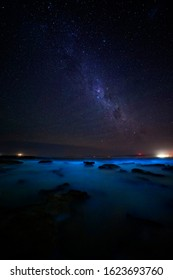 The ocean glowing a brilliant iridescent blue and glittering sparkly light from bioluminescent algae.  A magical phenomenon.  Twinkling stars overhead made a magical evening