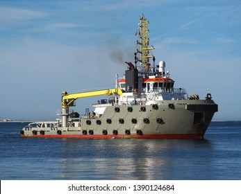 Ocean going towing vessel approaching ships berth at port facilities.