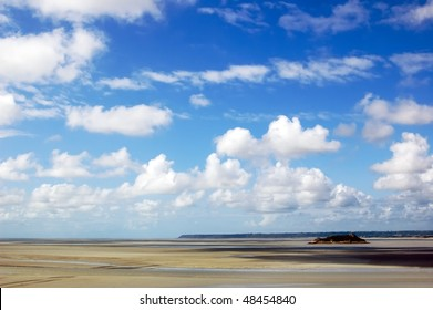 ocean at low tide under blue cloudy sky, at Mont Saint Michelle abbey, France