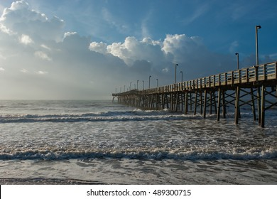 An ocean pier jutting out into amazingly vibrant skies and water.