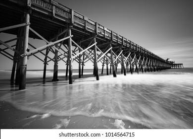 ocean pier wood and sand streaking water