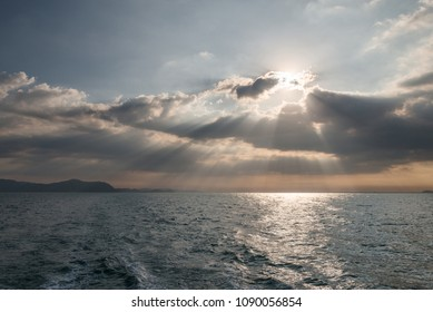 The ocean with the rays of light passing through the layers of clouds