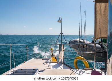 The ocean from the rear of a yatch on a sunny day with a lifeboat and some fishing rods