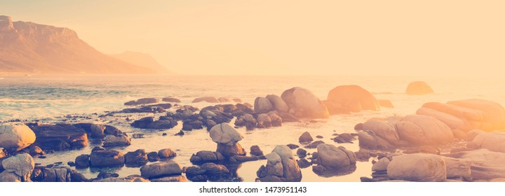 Ocean rock pools at sunset in South Africa with retro style filter effect