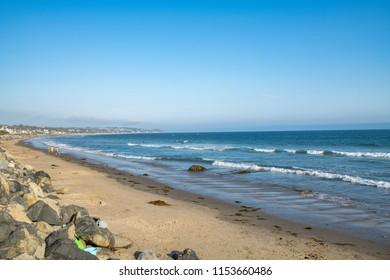 The ocean and sand on a Malibu beach in California.