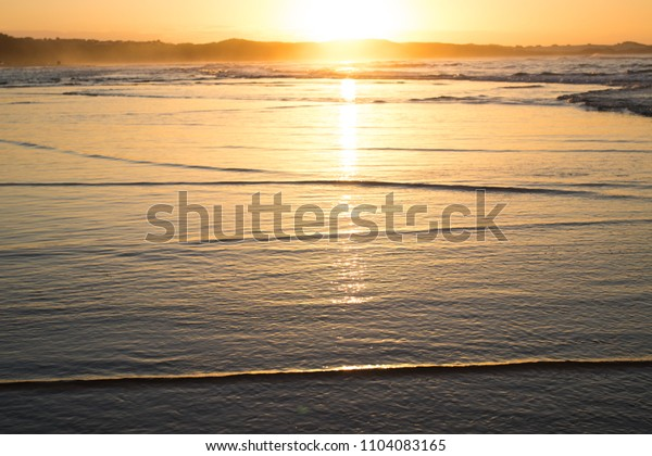 Ocean sea waves at sunset golden and blue reflection of the sun