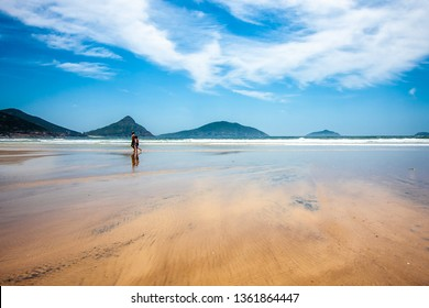Ocean shore at low tide. Wide sand space. Mountains on the horizon. A man and a boy are walking through it.  Fingal Bay, Australia