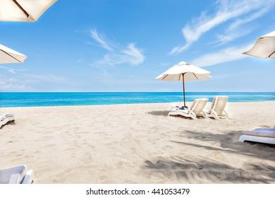 Sillas y sombrillas oceánicas con cielo y agua azules que dan un bello horizonte