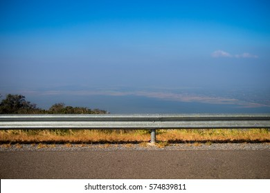 Ocean side highway and gard rail, Behide is beautiful mountain view and blue sky.Road side view mountain and sea background.Side road with mountain and blue sky view