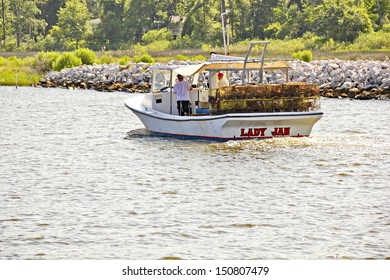 OCEAN SPRINGS, MISSISSIPPI - JUNE 27:  A boat with two fishermen with half empty crab cages returns from the morning on Biloxi Bay to an Ocean Springs marina on June 27, 2013 in a slow crab season.