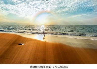 An Ocean Sunset With a Girl on the Beach As A Rainbow and Sun rays Shine Over the Ocean