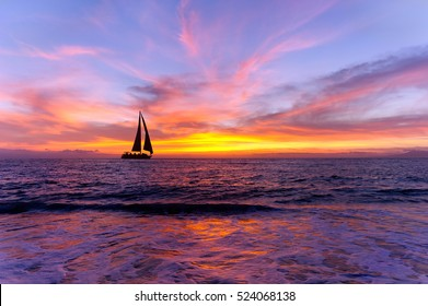 Ocean sunset sailboat silhouette is sailboat sailing along the ocean water with a colorful vivid sunset sky.