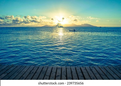 Ocean sunset from a wooden dock with kayak, sailboat, and mountain