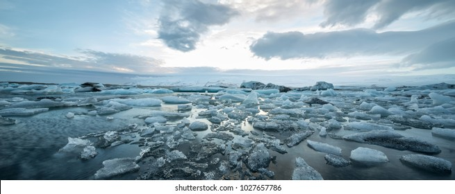 Ocean surface with ice floes on the background of the snow mountains and cloudy sky in Iceland. Sunlight reflected on the water surface. Horizontal.