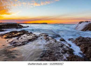 Ocean tide cascading over the rocks at Currumbin Rock Gold Coast, with a colourful sunset in the skies