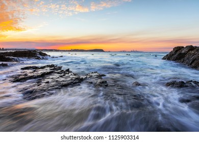 Ocean tide going out through the rocks with a colourful sunset at Currumbin Gold Coast