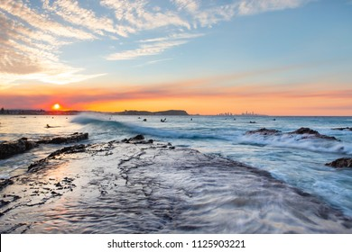 Ocean tide washing over a flat rock, with a colourful sunset in the skies at Currumbin Rock Gold Coast.