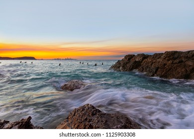 Ocean tide washing over the rocks at Currumbin Rock with a colourful sunset in the skies.